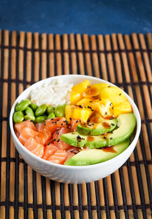 Salmon Poke bowl Raw fish salad Asian trendy food, mango, soy beans edamame, rice, avocado, served in bowl, blue dark background. Copyspace. Fast healthy lunch, selective focus, nutrition concept.