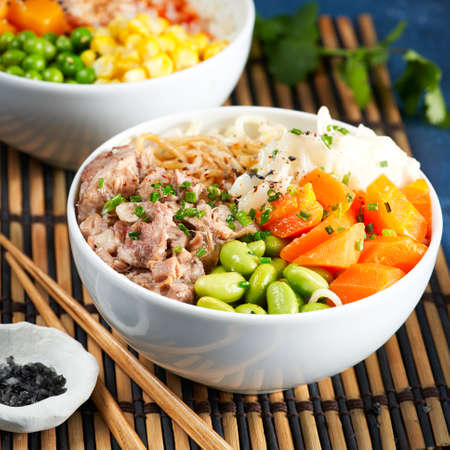 Two assorted poke bowls, pulled pork, vegetables, pumkin, soy beans edamame, noodles, on bowl, chopsticks. Closeup. Trendy asian food. Healthy, clean eating concept, blue dark background.