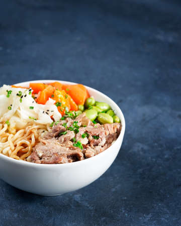 Poke bowl, pulled pork, vegetables, pumkin, soy beans edamame, noodles, on bowl, chopsticks. Copy space, closeup. Hawaiian dish, blue dark background. Trendy asian food. Healthy, clean eating concept.