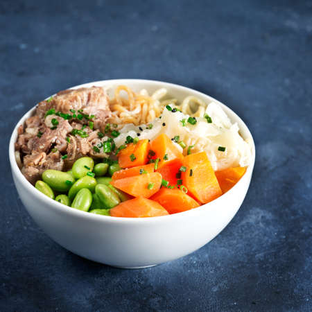Poke bowl, pulled pork, vegetables, pumkin, soy beans edamame, noodles, on bowl, chopsticks. Copy space, closeup. Trendy asian food. Healthy, clean eating concept. Hawaiian dish, blue dark background.