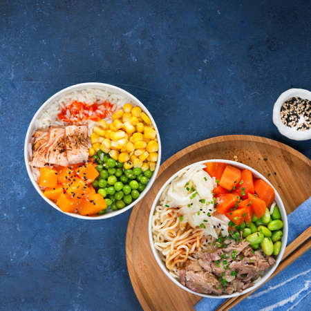 Two assorted poke bowls, flamed salmon, pulled pork, vegetables, rice, sauces. Top view, close-up. Hawaiian dish, blue dark background. Healthy and clean eating concept. Trendy asian food.