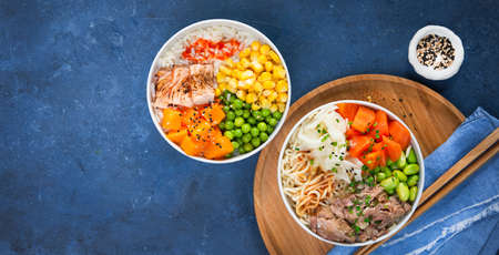 Food banner, two assorted poke bowls, flamed salmon, pulled pork, vegetables, rice, sauces. Top view, closeup. Hawaiian dish, blue dark background. Healthy and clean eating concept. Trendy asian food.