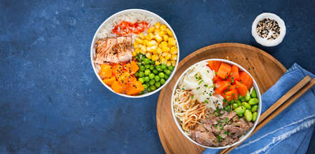 Two assorted poke bowls, flamed salmon, pulled pork, vegetables, rice, sauces. Top view, close-up. Hawaiian dish, blue dark background. Healthy and clean eating concept. Trendy asian food. 写真素材 - 165395092