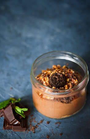 Delicious dessert chocolate mousse with chocolate cookies, almonds in glass jar on a dark blue concrete background, copy space. Selective focus. Homemade Raw Vegan Chocolate Pudding.
