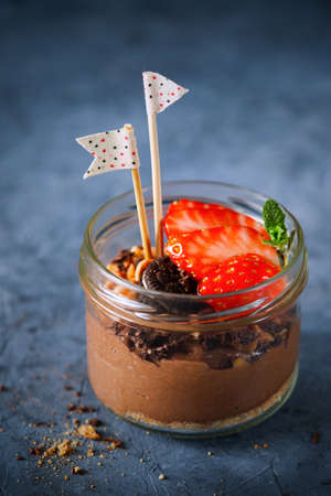 Easy dessert, chocolate cheesecake mousse with strawberries decorated with mint leaves. On a dark gray blue surface, copy space, close-up. Selective focus. Homemade Raw Vegan Chocolate Pudding.