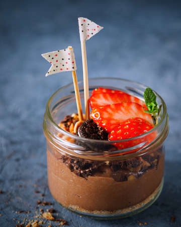 Easy dessert, chocolate cheesecake mousse with strawberries decorated with mint leaves. On a dark gray blue surface, copy space. Selective focus. Homemade Raw Vegan Chocolate Pudding. Close-up. 写真素材