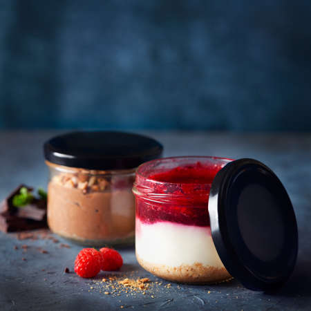 Two homemade easy cheesecakes in jars with chocolate mousse and raspberry curd sauce on a dark blue background. Selective focus. Homemade Raw Vegan Pudding. Healthy dessert.