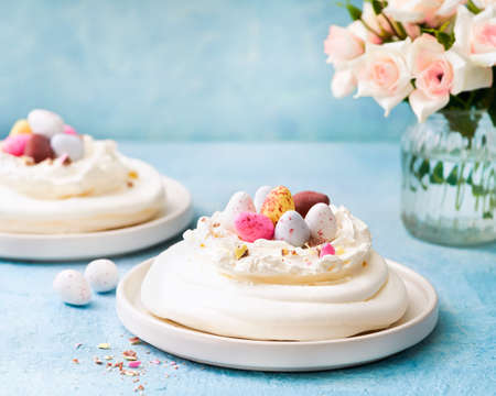 Meringue nest cake with colorful chocolate eggs, buttercream frosting on light blue background with copy space. Selective focus. Food ideas for kids. Easter cake. Close up. Spring love feast concept.