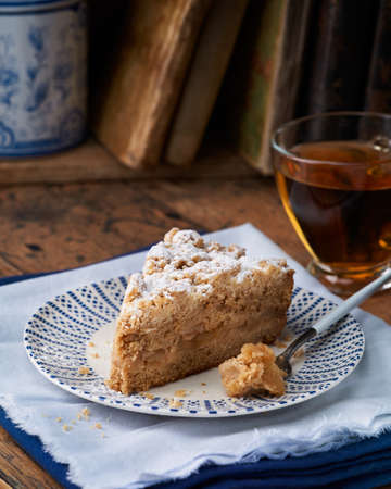 Piece of Apple streusel Crumble Cake pie with crumblesand tea on wooden background. Selective focus, rustic style. Homemade healthy dessert concept.