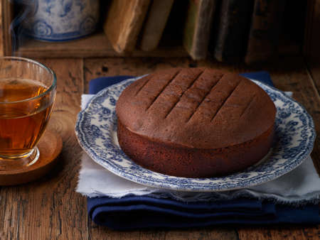 Homemade chocolate cake with hot cup of tea on wooden background, close up, rustic style, selective focus.