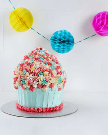 Birthday Smash Cake Giant Cupcake on light surface, copy space. Celebration party concept.