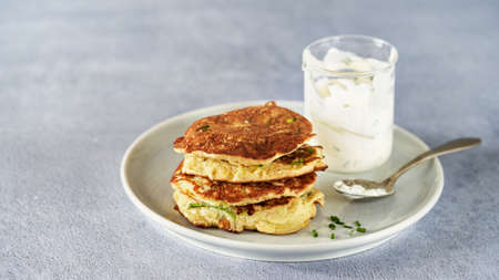 Vegetable zucchini fritters in stack with sour cream and chive, light background, copy space. Clean Healthy vegetarian food. 版權商用圖片