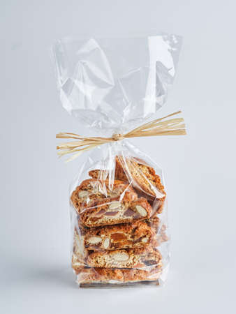 Pile of dried fruits Biscotti Cantucci Biscuits Cookies in plastic wrap packaging for sale. Italian dessert cookies close up, selective focus, copy space. Homemade bakery confectionery concept.