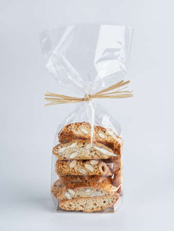 Pile of almond nuts Biscotti Cantucci Biscuits Cookies in plastic wrap packaging for sale. Italian dessert cookies close up, selective focus, copy space. Homemade bakery confectionery concept.