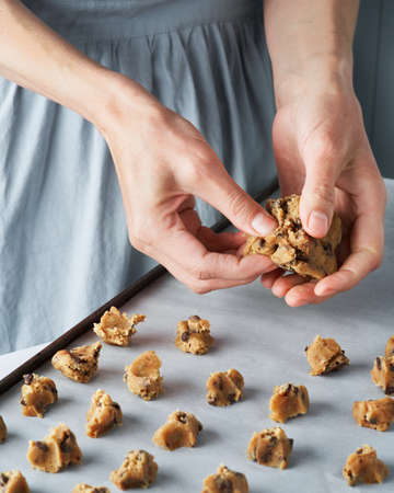 Close up woman's hands cooking homemade chocolate chips cookies in the home kitchen. Selective focus. Homemade dessert bakery concept. Foto de archivo