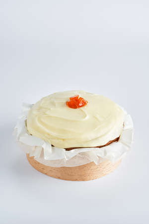 Sweet baked mini carrot cake with cream cheese frosting on recycle Mini Wooden Baking Mold, white background, space for text, selective focus.