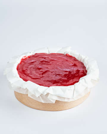 Mini cheesecake with red fruits jam topping on recycle Mini Wooden Baking Mold, white background, space for text, selective focus.