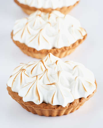 Close-up Lemon Curd and Meringue Mini Tarts Pies on white background, selective focus, space for text. Bakery pastry dessert concept. Foto de archivo