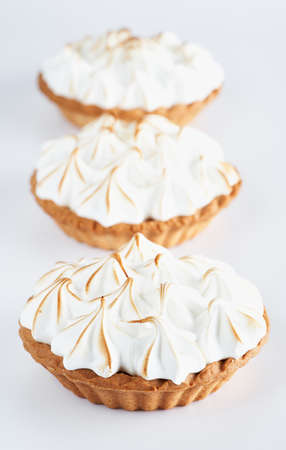 Lemon Curd and Meringue Mini Tarts Pies on white background, selective focus, space for text. Bakery pastry dessert concept.