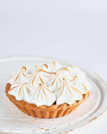 Lemon Curd and Meringue Mini Tart Pie on white background, selective focus, space for text. Bakery pastry dessert concept.