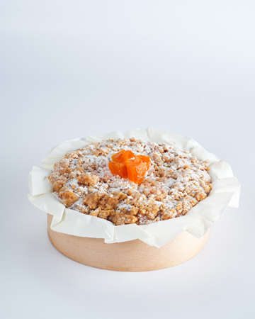 Baked mini crumble cake with dried fruits on recycle Mini Wooden Baking Mold, white background, space for text, selective focus. Homemade pastry, cooking cakes concept. Foto de archivo