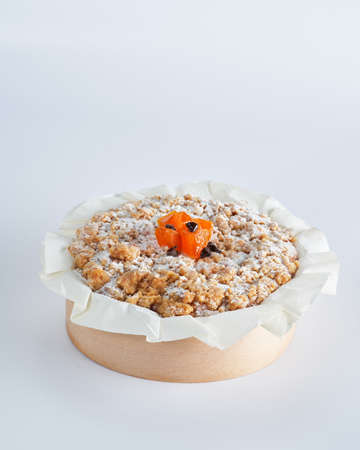 Baked mini crumble cake with dried fruits and chocolate chips on recycle Mini Wooden Baking Mold, white background, space for text, selective focus. Homemade pastry, cooking cakes concept.