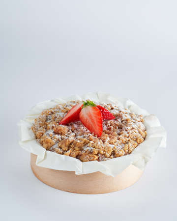 Baked strawberry mini crumble cake on recycle Mini Wooden Baking Mold, white background, space for text, selective focus. Homemade pastry, cooking cakes concept. Foto de archivo