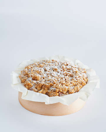 Baked mini crumble cake on recycle Mini Wooden Baking Mold, white background, space for text, selective focus. Homemade pastry, cooking cakes concept.