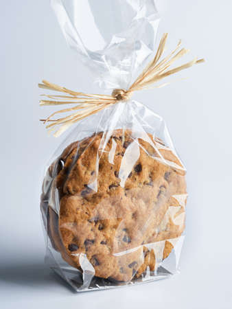 Big Soft and Crumbly Chocolate Chip Cookies in plastic wrap packaging for sale. Close up view, selective focus, space for text. Sweets for sale in supermarket. Natural and proximity products.