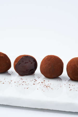 Chocolate truffles on a marble cutting board, white background, copy space. Selective focus. Close up. Dessert concept. Foto de archivo