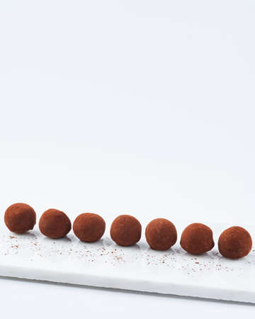 Chocolate truffles on a marble cutting board, white background, copy space. Selective focus. Dessert concept.