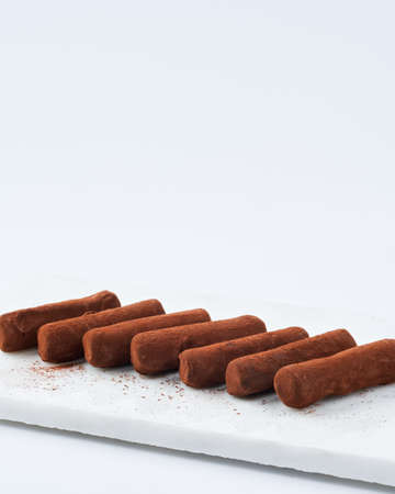 Chocolate truffles on a marble cutting board, white background, space for text. Selective focus. Japanese dessert.
