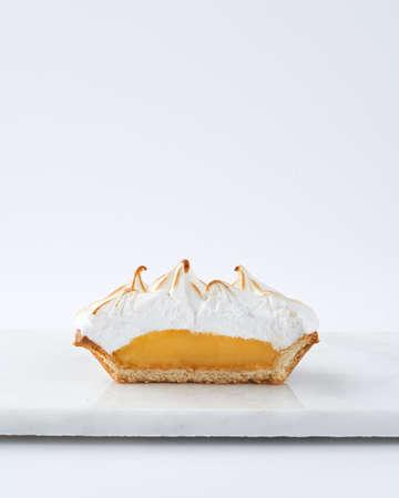Cut interior Lemon Curd Meringue Mini Tart Pie on white background, selective focus, space for text. Bakery pastry dessert concept.