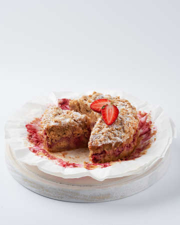 Sweet baked crumble mini cake with strawberry filling on white background, space for text, selective focus. Foto de archivo