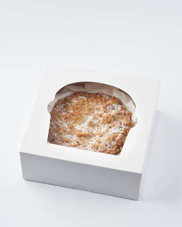 Sweet baked crumble cake in a takeaway cake box on white background, copy space. Selective focus. Foto de archivo