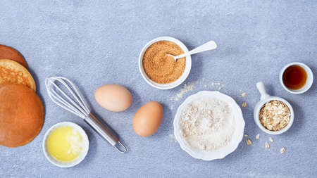 Banner food background. Ingredients for homemade oat pancake with whole grain oat, coconut sugar, vanilla syrup, organic eggs on light blue background. Healthy food recipe. Copy Space. Top view.