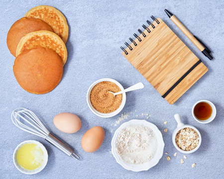 Food background. Ingredients for homemade oat pancake with whole grain oat, coconut sugar, vanilla syrup, organic eggs on light blue background. Healthy food recipe. Copy Space. Top view.