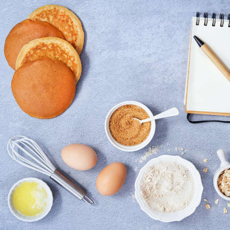 Ingredients for homemade oat pancake with whole grain oat, coconut sugar, vanilla syrup, organic eggs notebook in a pen on light blue background. Healthy food recipe photography. Top view. Copy Space for text.