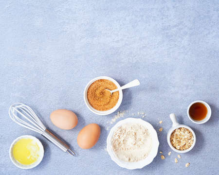 Ingredients for homemade oat pancake with whole grain oat, coconut sugar, vanilla syrup, organic eggs on light blue background. Healthy food recipe photography. Top view. Copy Space for text.