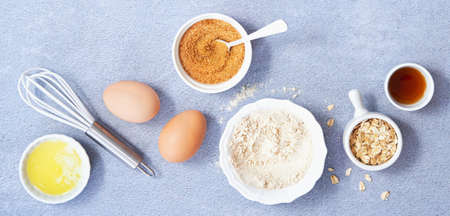 Food Banner. Ingredients for homemade oat pancake with whole grain oat, coconut sugar, vanilla syrup, organic eggs on light blue background. Healthy food recipe photography. Top view.