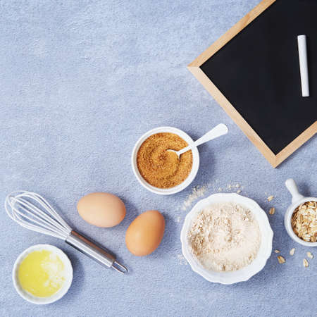 Ingredients for homemade oat pancake with whole grain oat, coconut sugar, vanilla syrup, organic eggs next to black chalkboard in a pen, light background. Healthy food recipe. Top view. Space text. Foto de archivo