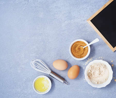 Ingredients for homemade oat pancake with whole grain oat, coconut sugar, vanilla syrup, organic eggs next to black chalkboard on light blue background. Healthy food recipe. Top view. Space for text.