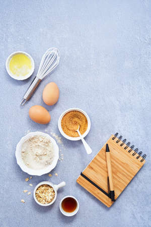 Ingredients for homemade oat pancake, whole grain oat, coconut sugar, vanilla syrup, organic eggs a notebook in a pen on light blue background. Healthy food recipe photography. Copy space. Top view.