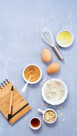 Ingredients for homemade oat pancake with whole grain oat, coconut sugar, vanilla syrup, organic eggs next to a notebook in a pen on light blue background. Healthy food recipe. Top view. Copy Space.