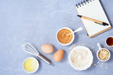 Healthy Food Background, Ingredients for homemade oat pancake with whole grain oat, coconut sugar, vanilla syrup, organic eggs next to a white notebook in a pen on light blue background. Space text.