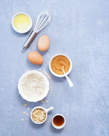 Food Background, Ingredients for homemade oat pancakes with whole grain oat, coconut sugar, vanilla syrup, organic eggs on light blue background.Top view. Copy Space. Healthy recipe concept.