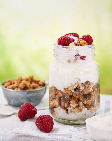 Granola with greek yogurt parfait fresh raspberries, coconut in a glass on wooden table outdoors. Healthy and tasty summer breakfast. Food background with Copy space. Foto de archivo