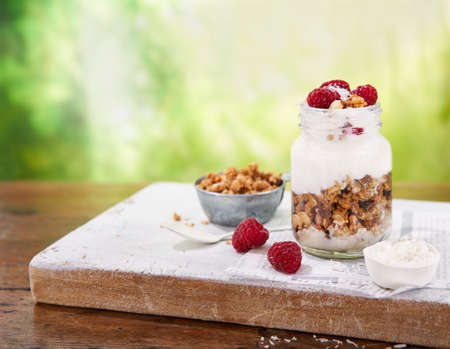 Granola with greek yogurt parfait fresh raspberries, coconut in a glass on wooden table outdoors. Summer Healthy and tasty summer breakfast.