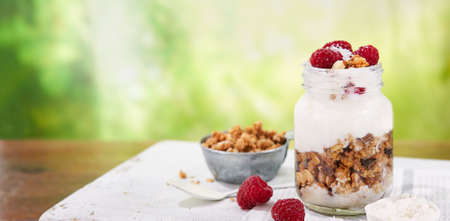 Granola with greek yogurt parfait fresh raspberries, coconut in a glass on wooden table outdoors. Healthy and tasty summer breakfast. Food Banner background with copy space. Foto de archivo