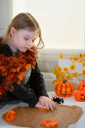 Concentrated girl makes traditional Halloween bat-shaped cookies. Holiday decoration party concept. Foto de archivo